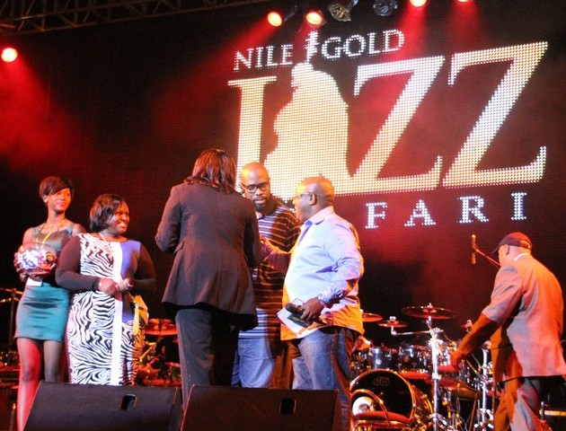 Event emcee Isaac Rucci presents the British Airways business class ticket winners at the Nile Jazz Safari