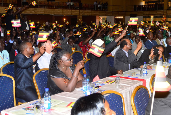 Participants wave Uganda flags during the National Consultation on Free and Fair Elections conference at Hotel Africana in Kampala yesterday. PHOTO BY DOMINIC BUKENYA