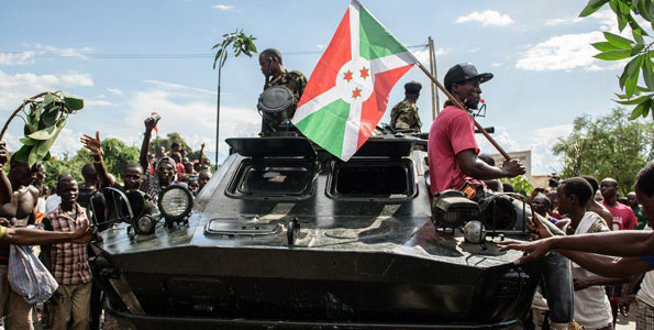 Men hold Burundi's flag as people take to the streets of Bujumbura to celebrate following the radio announcement by Major General Godefroid Niyombare that President Nkurunziza was overthrown on May 13, 2015. PHOTO | JENNIFER HUXTA |  AFP