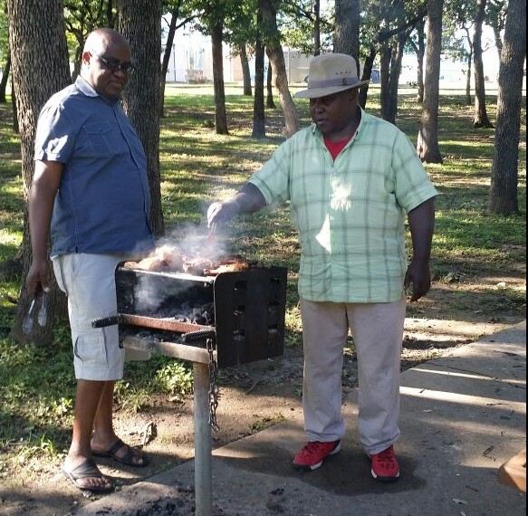 The Dallas ICOB Chapter Executive Secretary Rev. Joseph Kamugisha in red with others working the BBQ spit at a registration