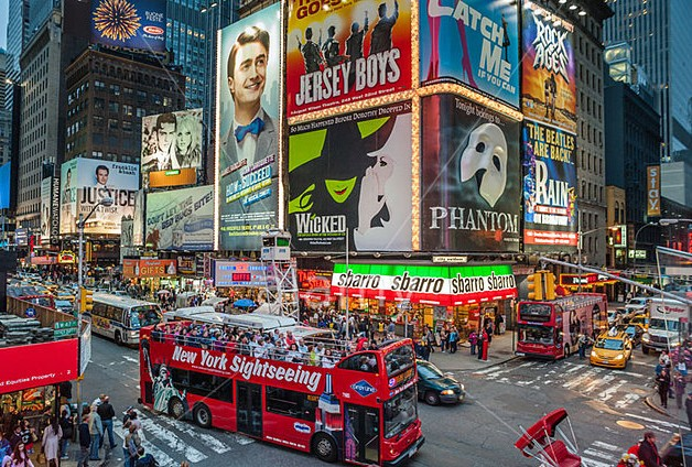 A sightseeing bus packed with tourists in Times Square New York City